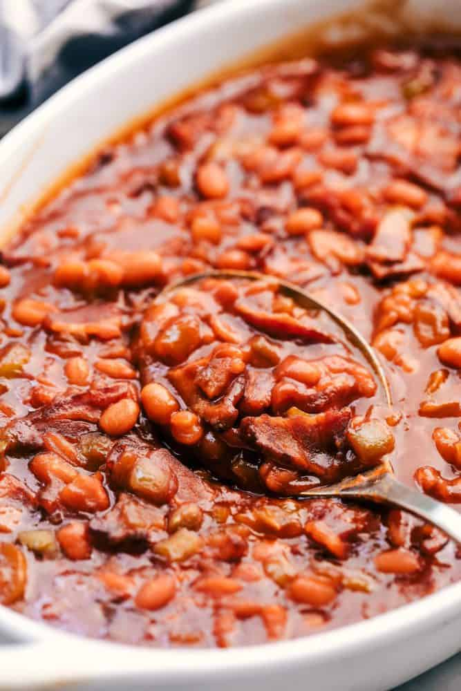 Baked beans in a white platter with a metal spoon.