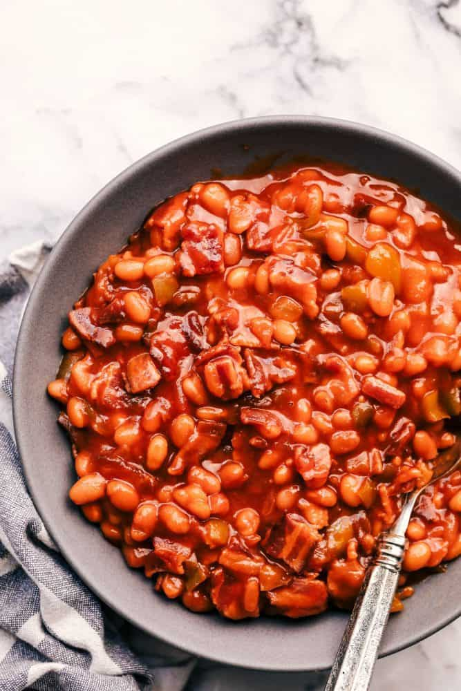 Baked Beans in a grey bowl with a metal spoon.