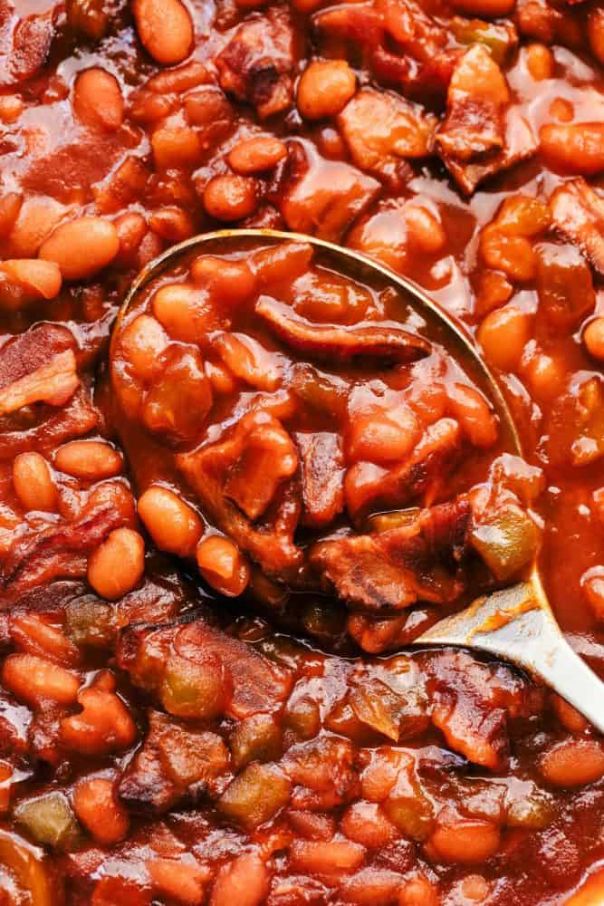 Close-up of baked beans with a metal spoon.