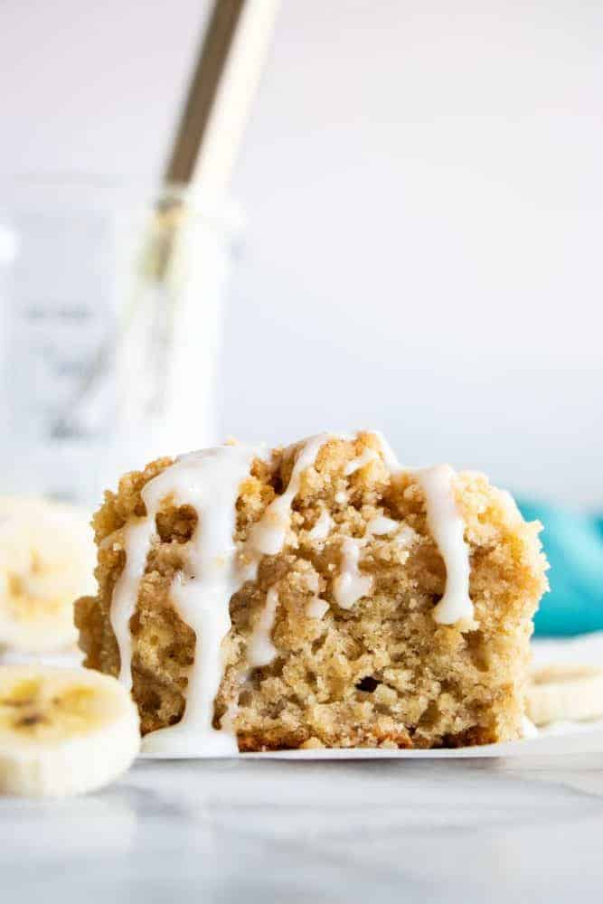 A slice of Banana Bread Crumb Cake with fresh cut bananas on the side.