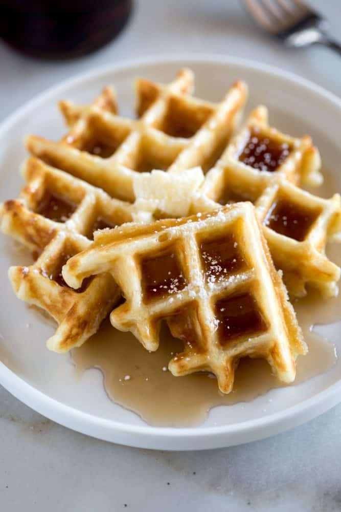 Belgian Waffles topped with syrup, and powdered sugar.