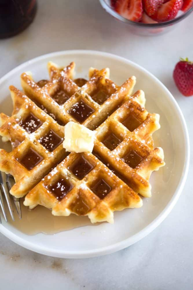 Belgian waffle on white plate topped with syrup, butter and powdered sugar.
