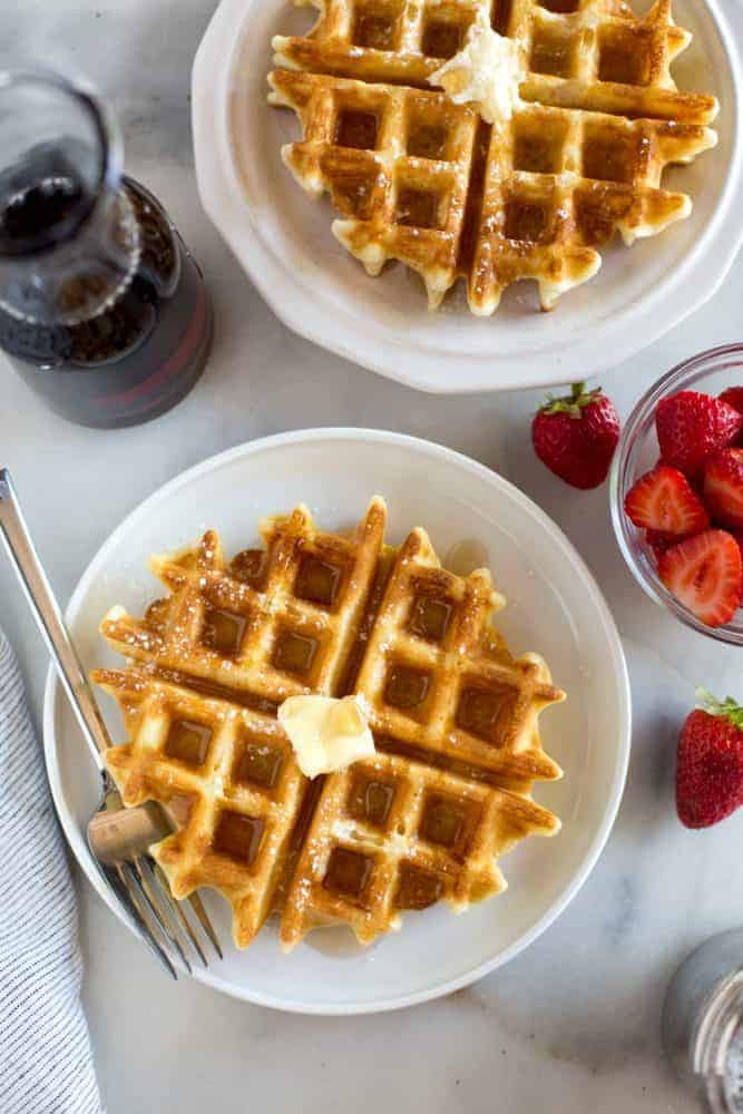 Overhead photo of two plates with belgian waffles on them, and syrup and strawberries on the side.