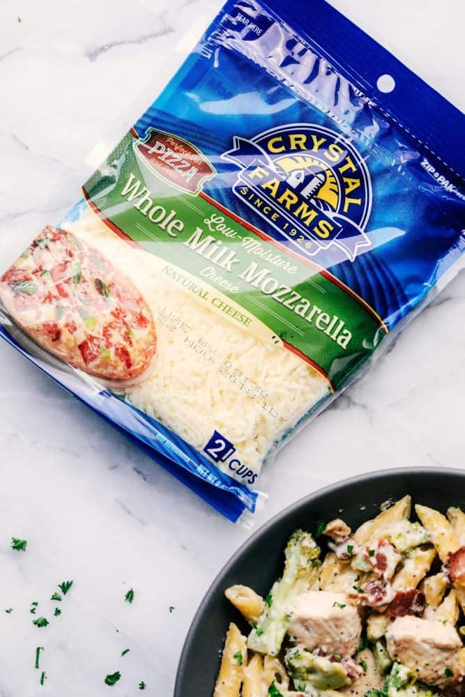 Cheesy Chicken, Bacon and Broccoli Ranch Pasta in a grey bowl with a package of Crystal Farms Whole Milk Mozzarella Cheese.