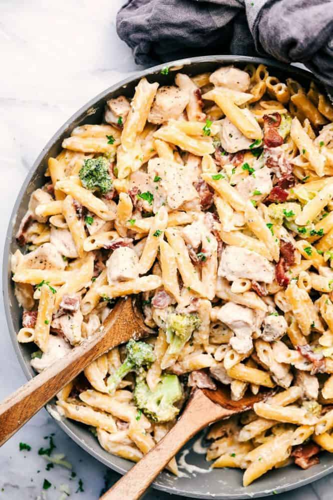 Large bowl of Cheesy Chicken, Bacon and Broccoli Ranch Pasta with two wooden spoons for serving.