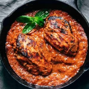 Creamy tomato basil chicken in a cast iron skillet ready to be served
