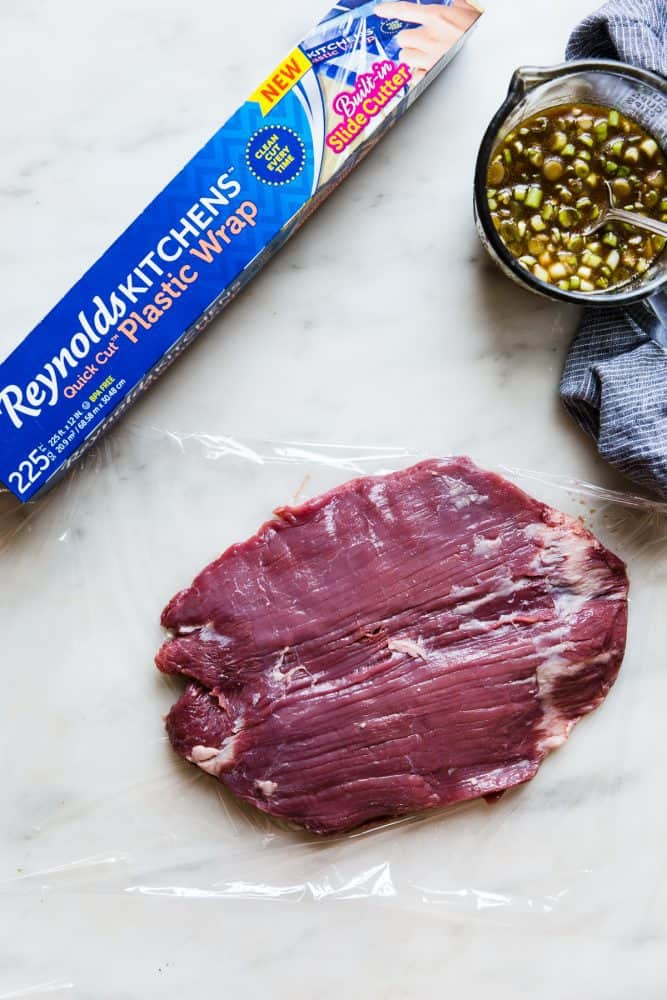 Un-cooked flank steak on a piece of Reynolds wrap.