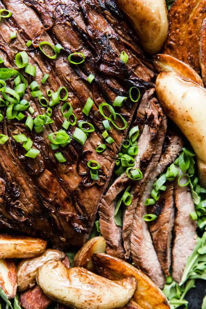 Close up of Brown Sugar Garlic Flank Steak with baked potato slices.