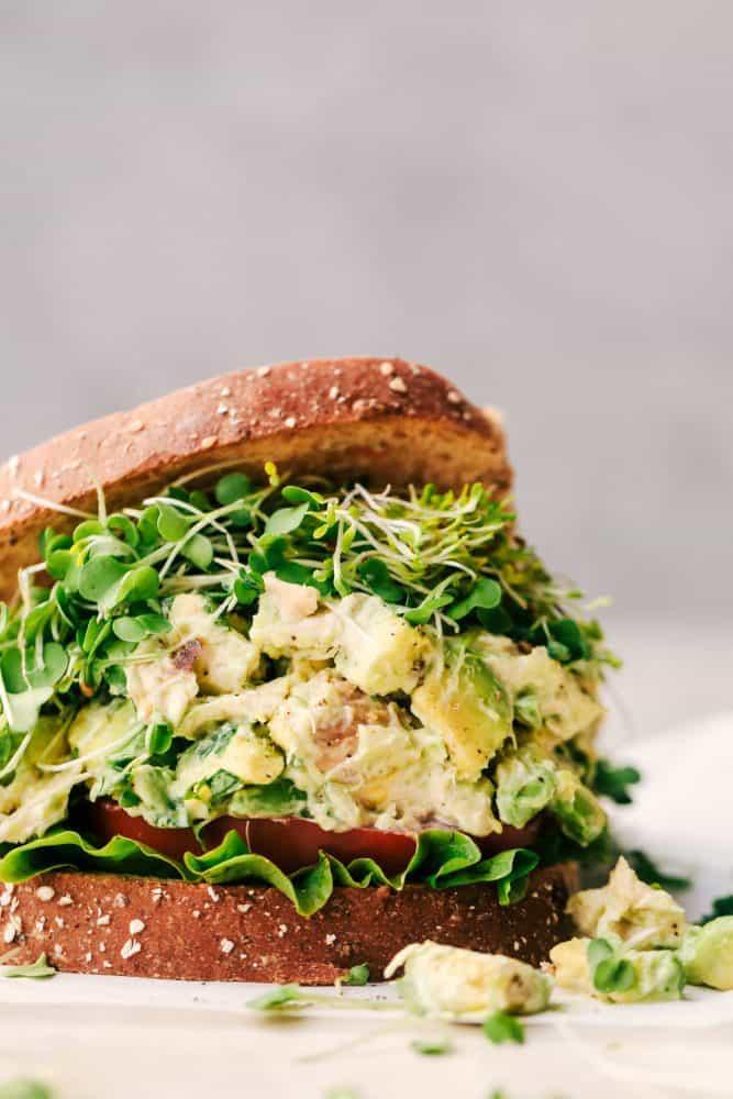 Avocado Chicken Salad between two slices of bread.