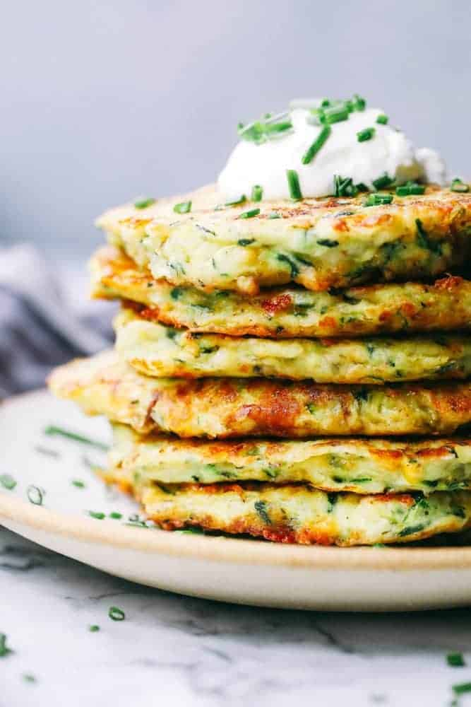 Cheesy Zucchini Fritters stacked on a white plate.