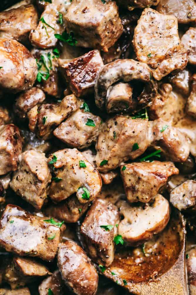 Up close photo of garlic steak bites with mushrooms and a wooden spoon in the lower right hand corner.