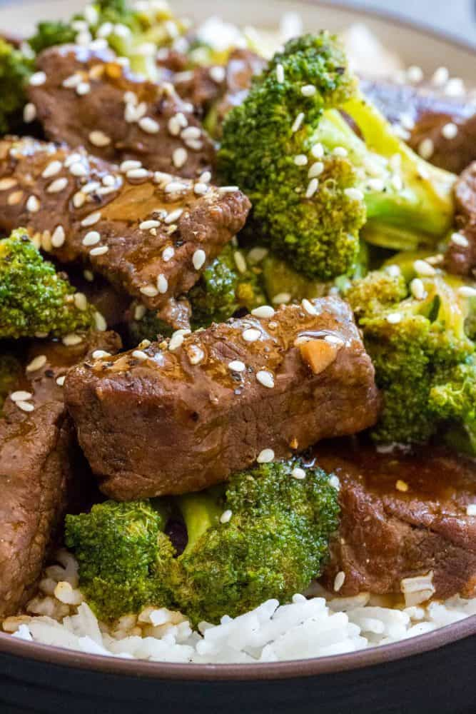 Close up photo of beef and broccoli topped with sesame seeds.