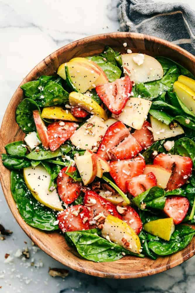 Strawberry, Apple, and Pear Spinach Salad in a wood bowl.