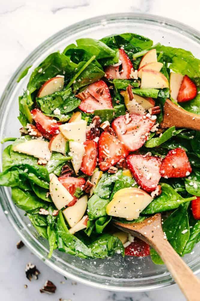 Strawberry, Apple, and Pear Spinach Salad in a clear bowl with a wooden spoon.