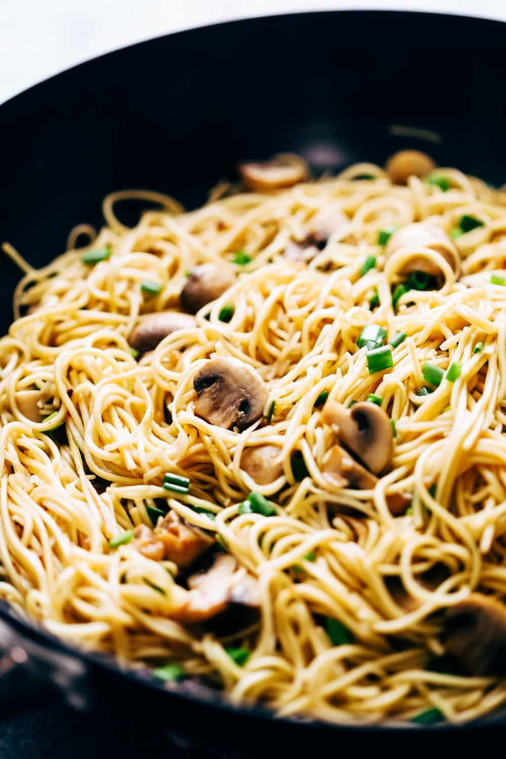 Closeup of garlic mushroom noodles in a wok