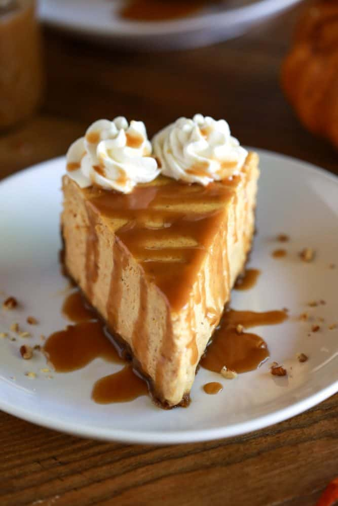 A slice of pumpkin cheesecake with caramel sauce on top.