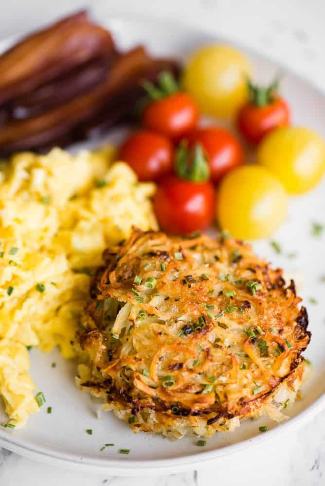 Baked Parmesan Hashbrowns on a white plate with eggs, bacon and small tomatoes.