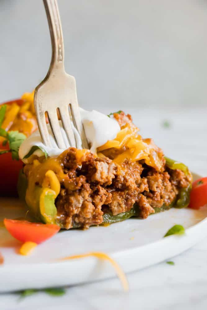 Taco Stuffed Pepper on a white plate with a fork.