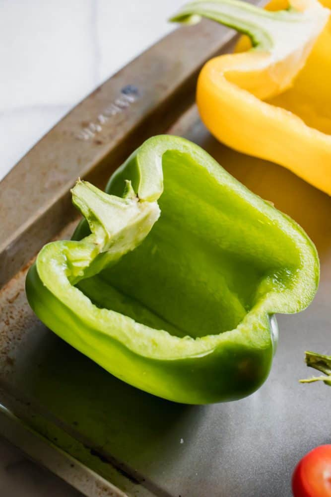 Bell peppers cut in half on a cookie sheet.