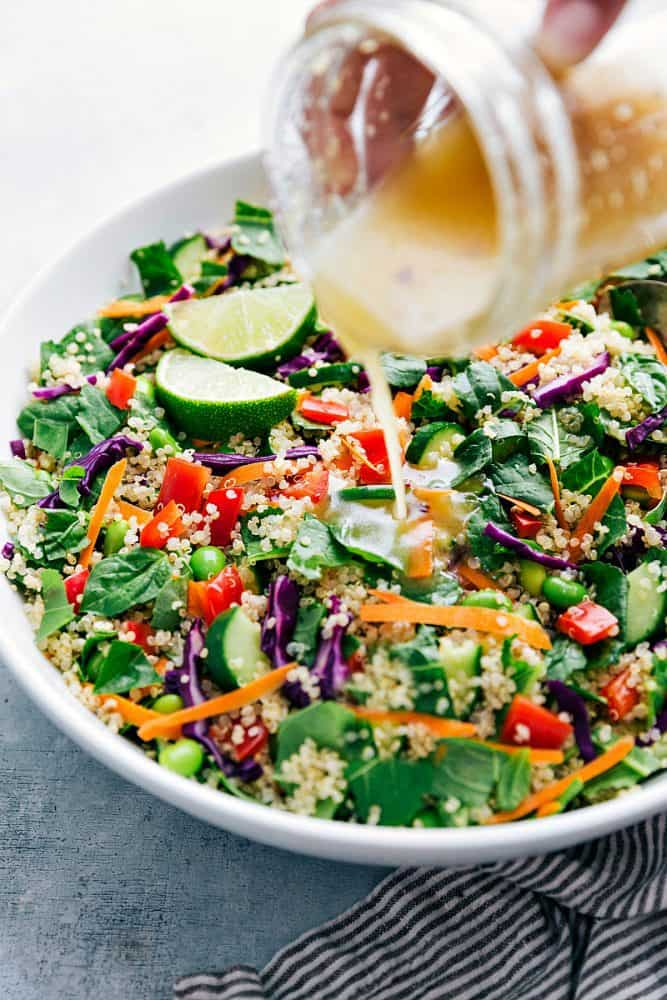 Thai quinoa salad in a white bowl with dressing being drizzled over the top.