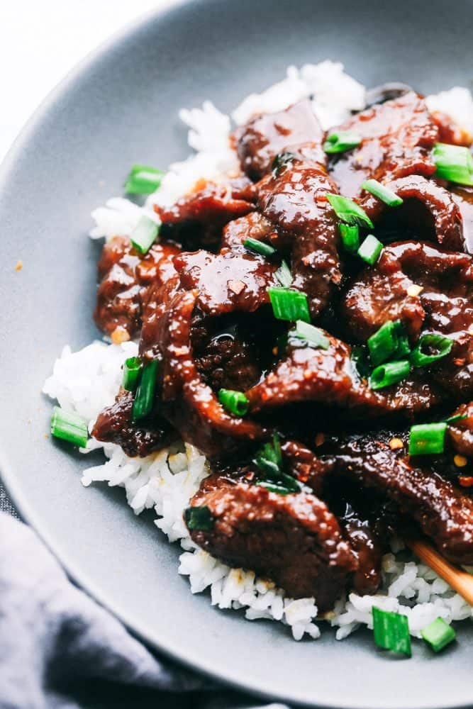 Mongolian Beef over white rice in a grey bowl.