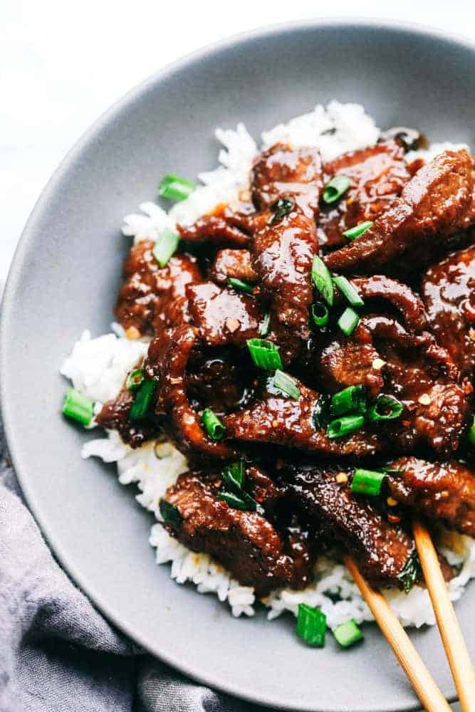 Mongolian Beef over white rice in a grey bowl with chopsticks.