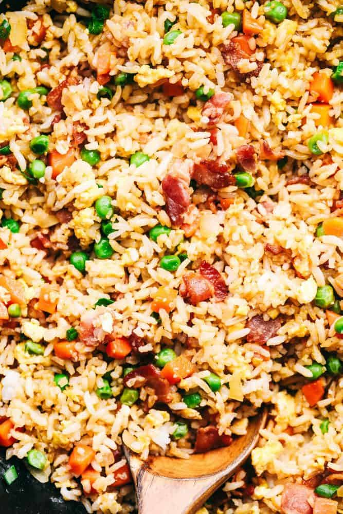 Close up of Bacon Fried Rice with a wooden spoon.