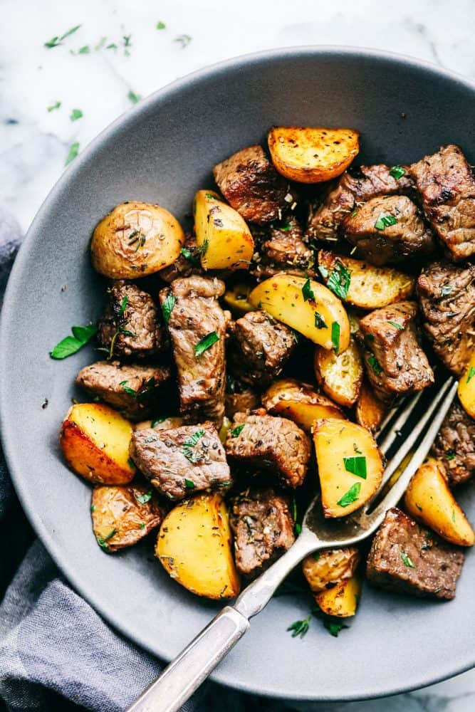 Garlic Butter Herb Steak Bites with Potatoes in a grey bowl with a metal spoon.