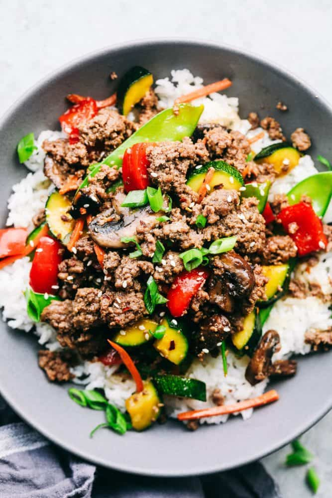 Korean ground beef stir fry over top white rice in a gray bowl.