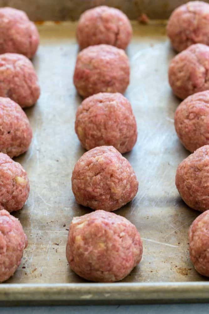 Raw meatballs lined up on a sheet pan.