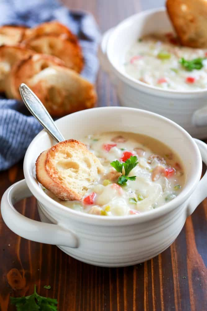 Creamy Clam Chowder in a large white cup with a slice of bread for dipping.