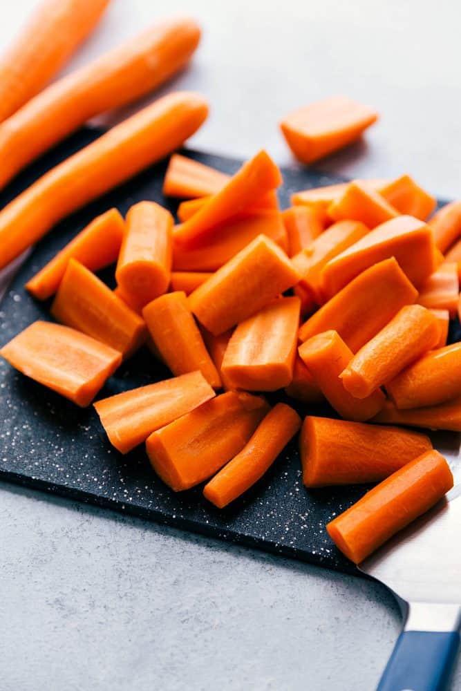Fresh carrots being cut on a cutting board.