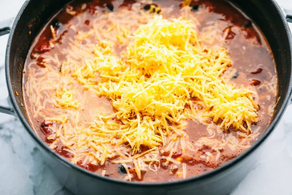 Large pot of Cheesy Taco Soup with freshly grated cheese on top.