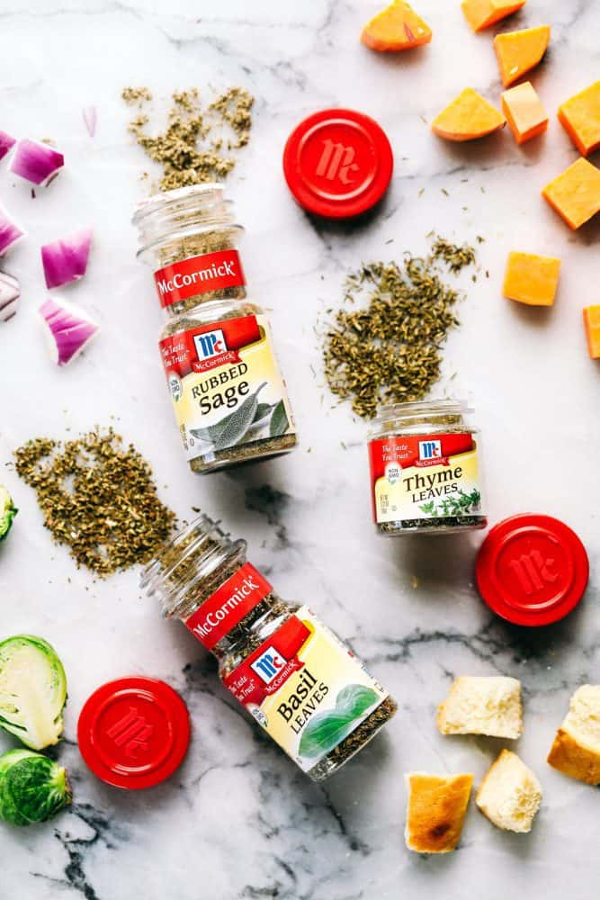 McCormicks seasoning's laid on a white granite countertop spread out with cheese, brussels sprouts and red onion. Rubs sage thyme leaves and basil leaves from McCormick seasoning are spread onto a white granite countertop.