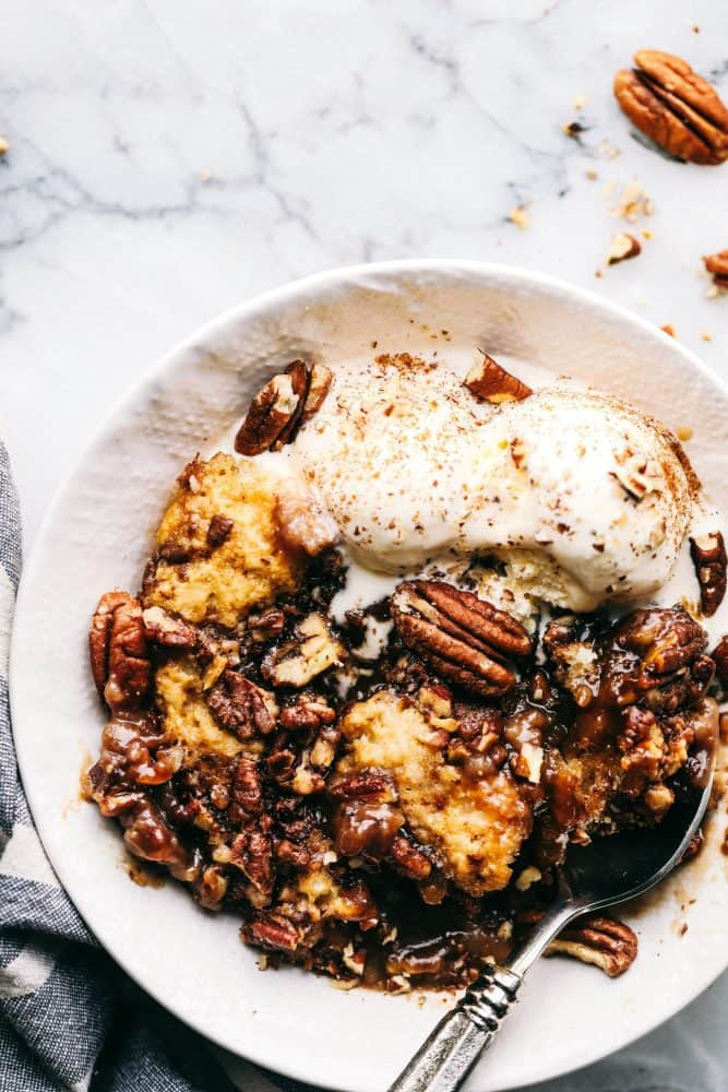 A white bowl full of Pecan Pie Cobbler with vanilla ice cream and a metal spoon.