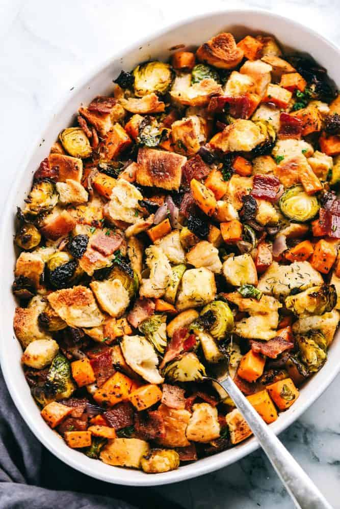 Roasted autumn vegetable stuffing on in a white baking dish with a silver spoon pulling up part of the stuffing.
