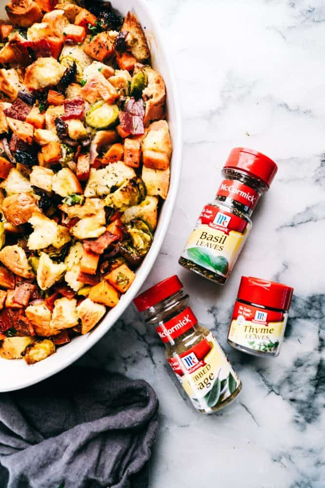 Roasted autumn vegetable stuffing and a white casserole dish with McCormick seasoning's on the side are the bottles of basil leaves, sage and thyme and their bottles.