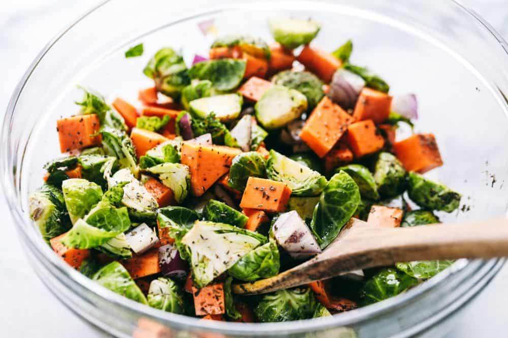 Chopped up carrots, brussels sprouts and red onions being stirred together with seasoning from McCormick using a wooden spoon and a glass bowl.