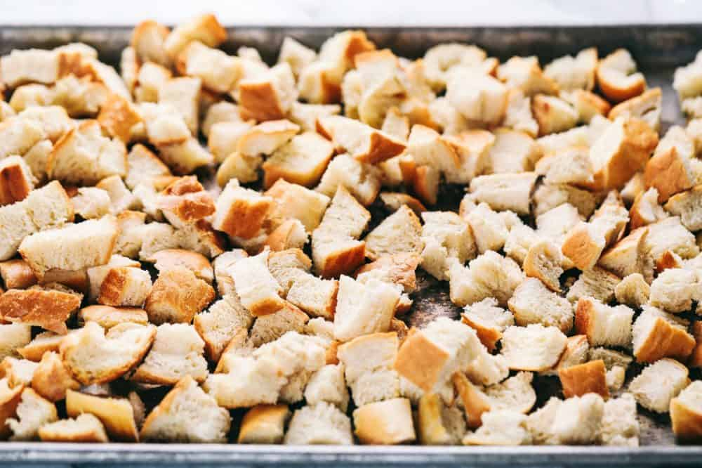 Chunks of bread on a baking sheet getting ready to be roasted to use in the Roasted autumn vegetable stuffing.