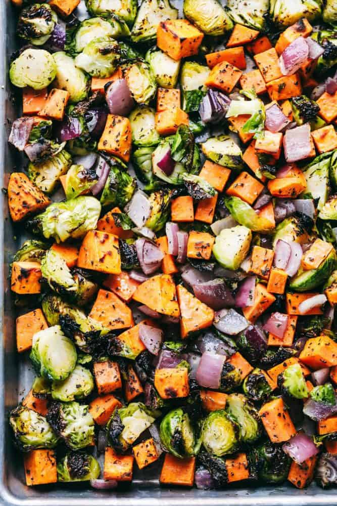 A baking sheet full of chopped up carrots, red onions and brussels sprouts with McCormick seasoning.