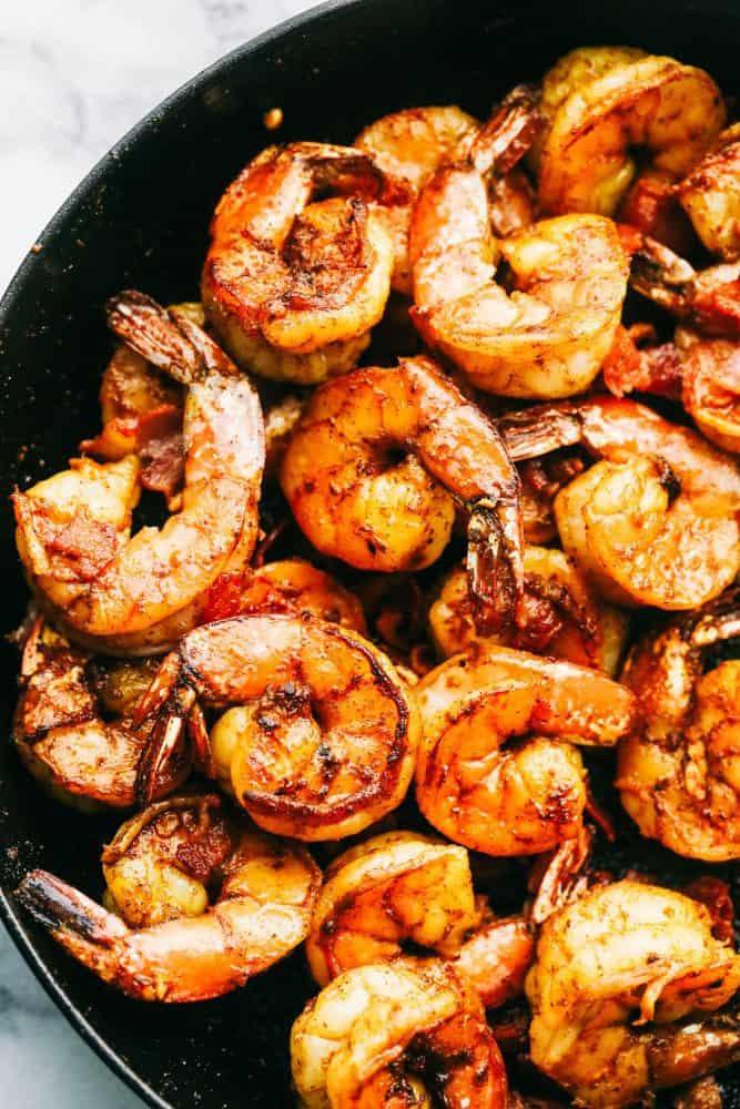 Close-up of Cajun garlic shrimp in a skillet.
