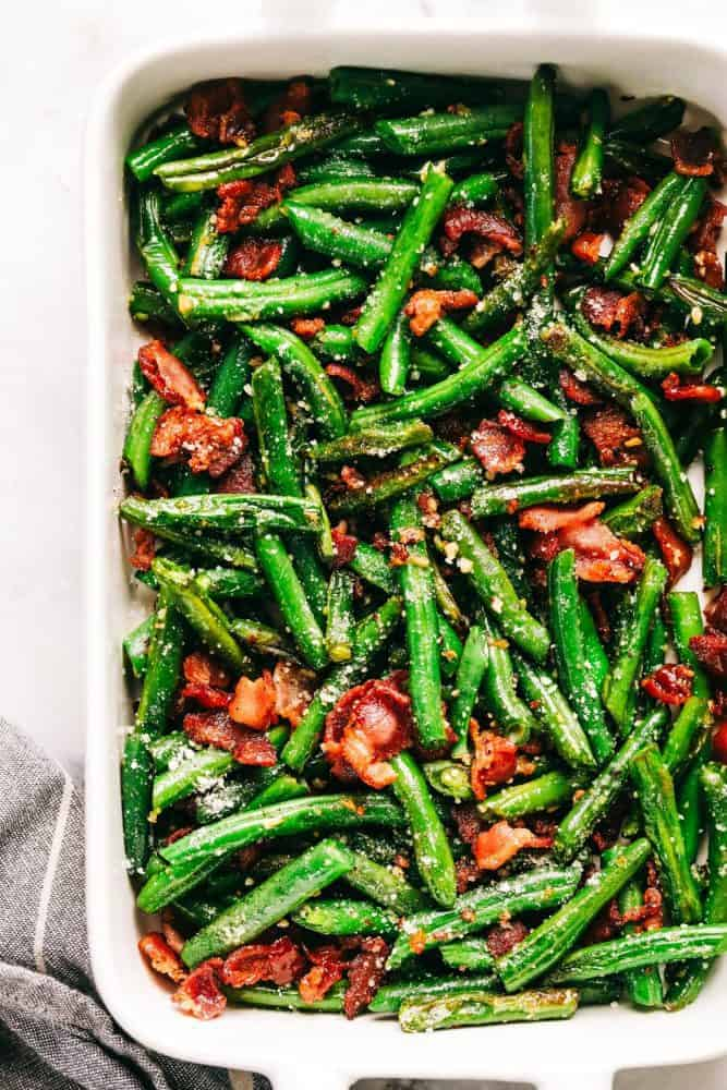 Garlic Parmesan Green Beans with Bacon cut up into the green beans in the white dish.