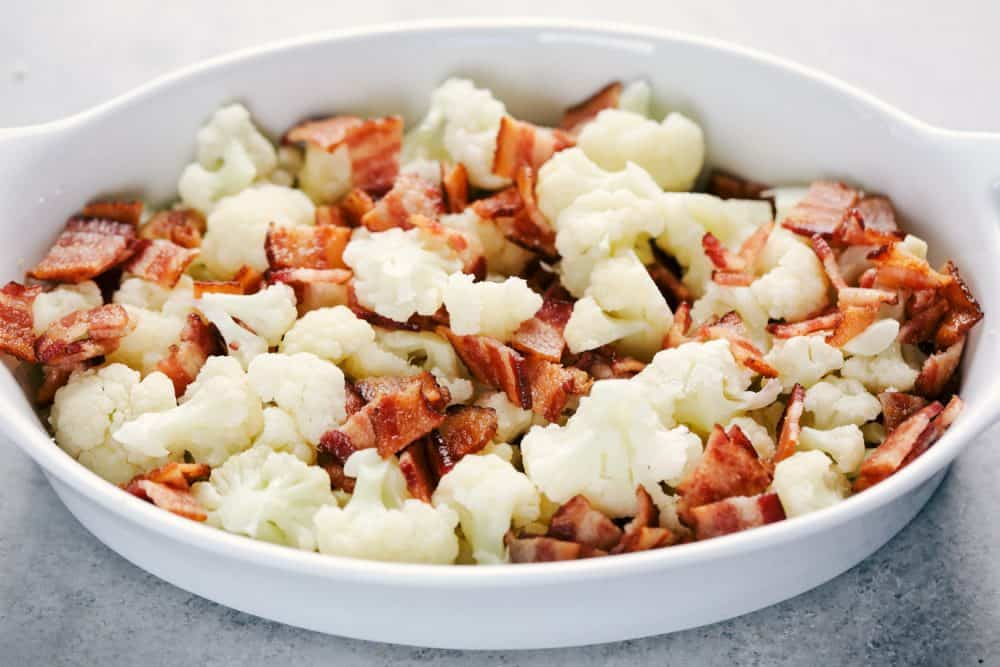 Chopped up cauliflower with Smithfield bacon pieces cut up in a white casserole dish being ready to bake.