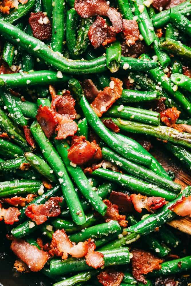 An up close photo of the garlic Parmesan green beans with the chopped up cooked bacon and garnished with Parmesan sprinkles.