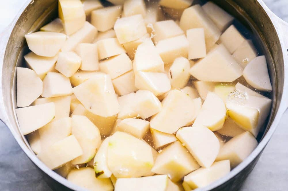 A sauce pan full of water with potatoes chopped into 1 inch pieces.