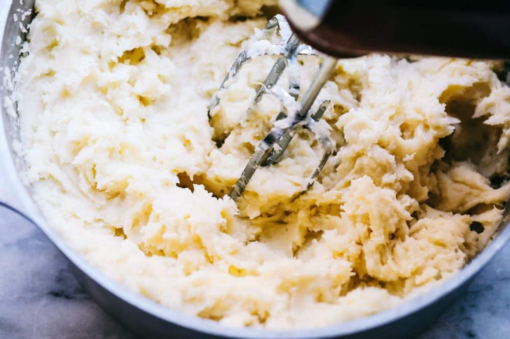 Mashed potatoes being blended together with a hand mixer in a sauce pan.