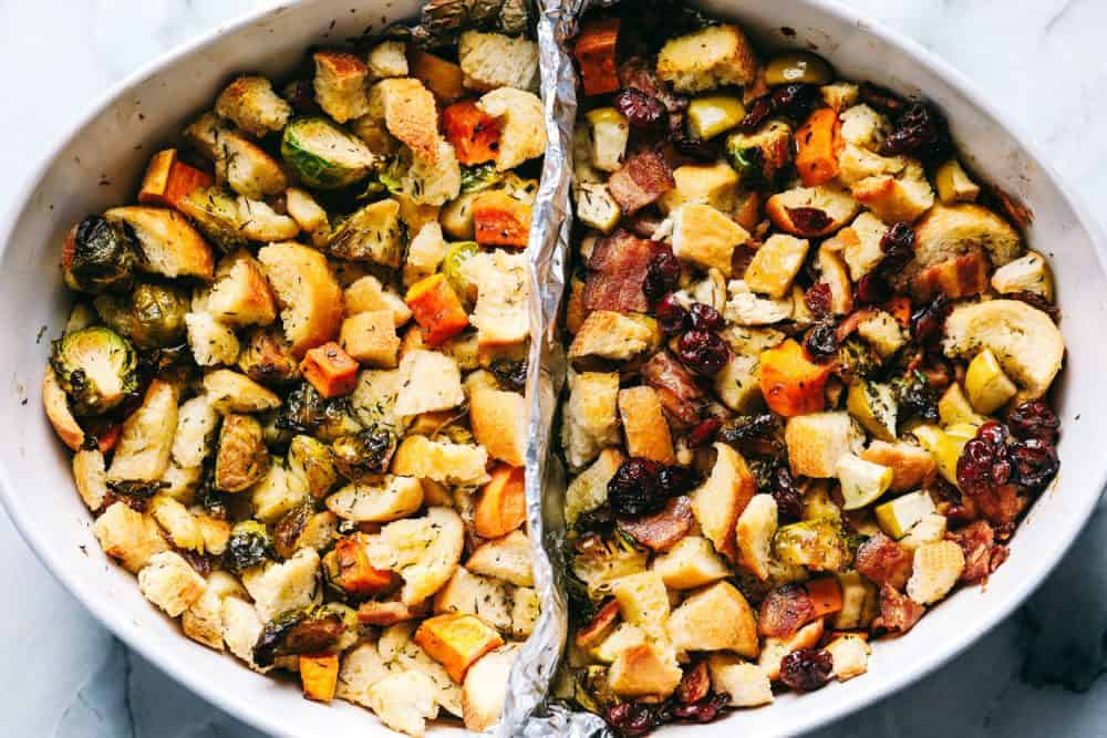 Roasted autumn vegetable stuffing and a white dish with an aluminum foil divider in the middle