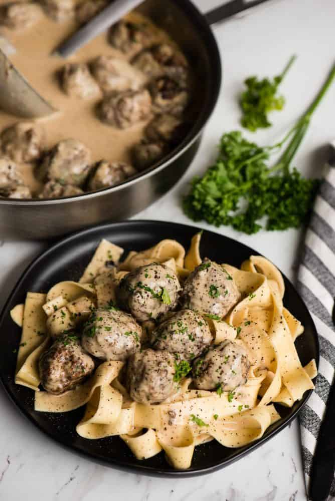 Swedish Meatball Pasta on a black plate garnished with fresh parsley