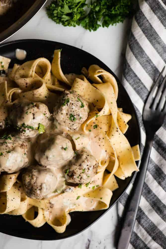 Swedish Meatball pasta on a black plate with a black fork on a napkin next to the plate on the righthand side.