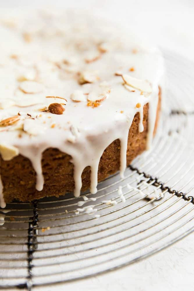Close up photo of brown butter almond cake on a cooling rack with sliced almonds on top.